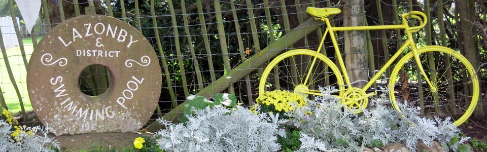 Photo: entrance to Lazonby Pool with yellow bike to mark the passing of the Tour of Britain